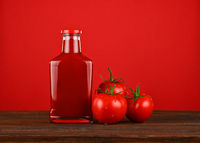 Bottle of ketchup and fresh tomatoes over red