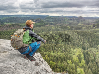 Climber man with backpack and trekking clothes on the top