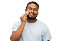 african american man cleaning face with cotton pad