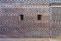Wall with black and red bricks with white seam and two small windows with metal bars