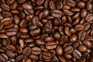 Roasted dark coffee beans background from close up.