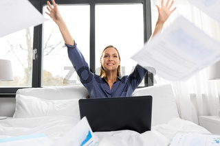 happy woman with laptop and papers in bed at home