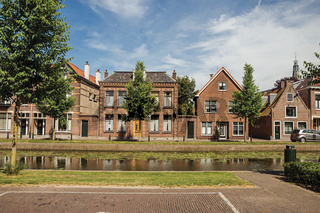 Canal with streets and brick houses in Weesp