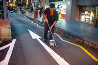 Singapore, A worker paints the arrow of a road marking with special road line paint