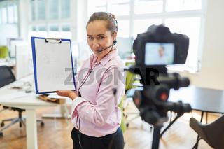 Business Frau mit Klemmbrett beim Video aufnehmen