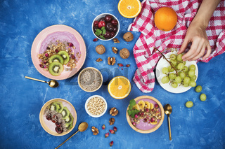 Flatlay with healthy vegan breakfast of berry plant-based yogurt with granola, chia seeds, various fruits and walnuts on blue background