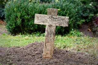 einfaches billiges Holzkreuz auf einem Armengrab