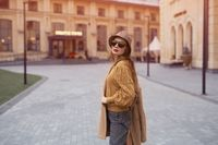 Turned from behind fashion model young woman in sunglasses and hanging on a shoulder autumn beige coat walking on the street happily posing for the camera. Tinted photo