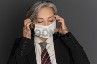 Grey-haired middle-aged business woman putting on a protective mask with eyes closed isolated on grey background. Portrait of modern senior woman in studio wearing business clothes