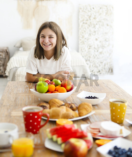 Joyful girl at table with tasty dishes