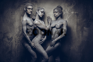 Naked sportive women painted in grey color posing over grey wall