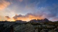 two hikers watching the sunset in the french alps