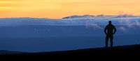 Hiker man silhouette standing at spectacular blue layered mountain ranges silhouettes. Sunset landscape in Iceland.