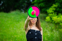A young girl plays a tennis ball on Velcro outdoors. Day off, sunny summer day.