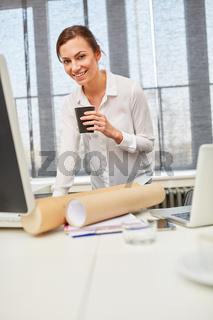 Frau im Büro trinkt Kaffee aus Plastikbecher