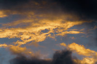 Stunning fluffy thunderstorm clouds illuminated by disappearing rays at sunset and dark thundercloud