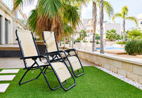 Two empty lounge chairs on artificial lawn grass inside of personal area backyard residential summer villa, view to modern homes with swimming pool, luxury, summer holidays lifestyle concept