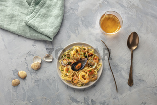 Seafood pasta. Tagliolini with mussels, shrimps, clams and squid rings, shot from the top with wine