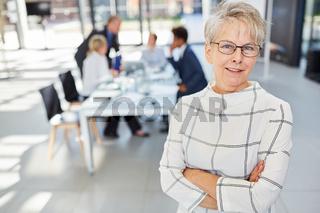 Seniorin als selbstbewusste Chefin vor ihrem Team