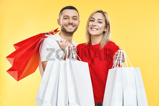 Young happy couple holding shopping bags in hands isolated over yellow background