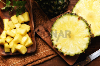 High angle shot of a fresh cut pineapple with knife on cutting board. Slices and a plate full of diced sections.
