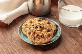 A closeup photo of chocolate chip cookies with milk on a dark rustic wooden background