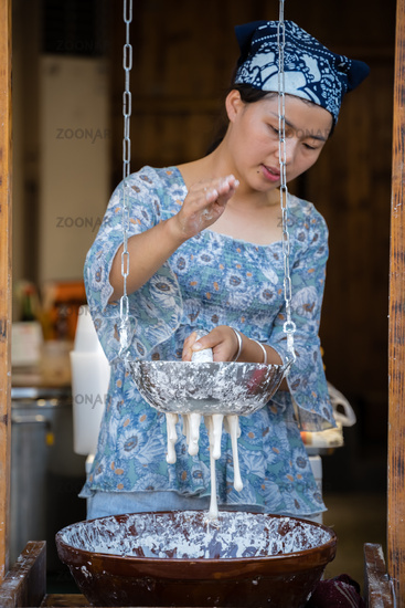 Woman making chinese noodles on market