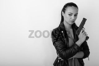 Studio shot of young Asian woman thinking while looking down and holding handgun against white background