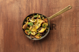 A photo of a rustic mushrooms and olives saute with mint, shot from above on a dark rustic background