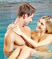 Mann trägt Frau im Wasser im Schwimmbad