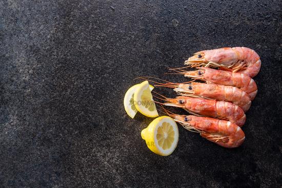 Boiled tiger prawns on black table. Tasty shrimps.