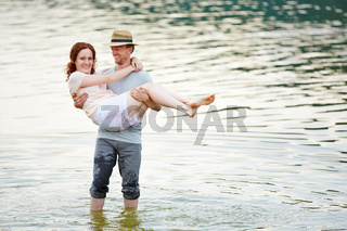 Mann trägt Frau im Wasser