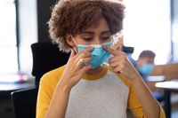Mixed race woman putting mask on in an office