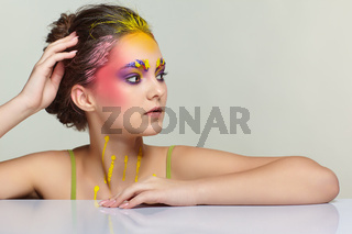 Female portrait with unusual face art make-up. Paint on brows, hair, around eyes and with paint drips on the neck.