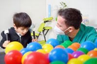 Physical therapist playing with children, with cerebral palsy