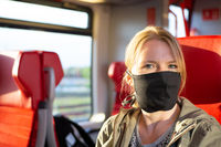 Woman travelling in a railway train wearing a self made face mask. Coronavirus and travel concept