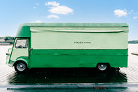 Green retro food truck parked on promenade by the sea