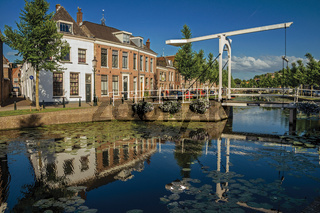 Canal with bascule bridge and brick houses on sunset in Weesp