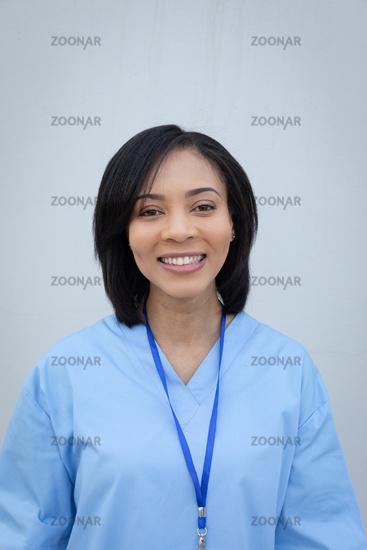 Portrait of female health professional against grey background