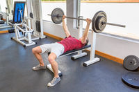 Young caucasian man bench press with barbell