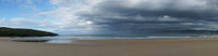panorama of an empty and large beautiful golden sand beach underneath a bad weather sky
