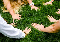 hands of people next to each other on green grass