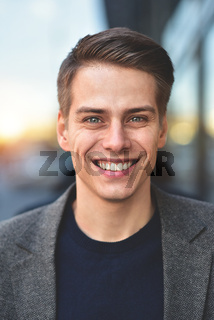 Portrait of stylish happy handsome young man standing outdoors.