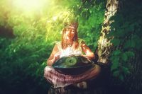 beautiful woman playing with hangdrum in nature. painting effect.