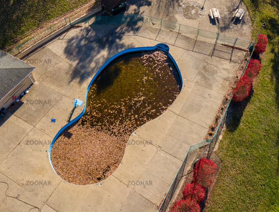Aerial drone photo of an uncovered swimming pool filled with fallen autumn leaves