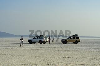 Zwei Geländewagen einer Reisegruppe stehen mehr als 100 Meter unter dem Meeresspiegel auf dem Assale Salzsee