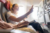 Casual young woman freshening up during airplane flight. Female traveler flying on commercial airplane seated in economy passanger cabin.