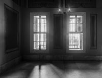 Black and white shot of two windows, revealing strong light into dark room with tiled marble floor