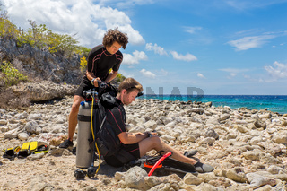 Two divers on the beach get ready for diving