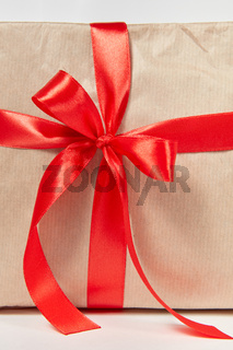 Big red bow from silk ribbon on a gift box. Close-up view.